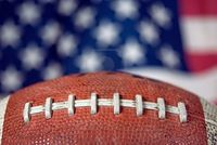 8607773-extreme-close-up-of-a-football-with-flag-background.jpg
