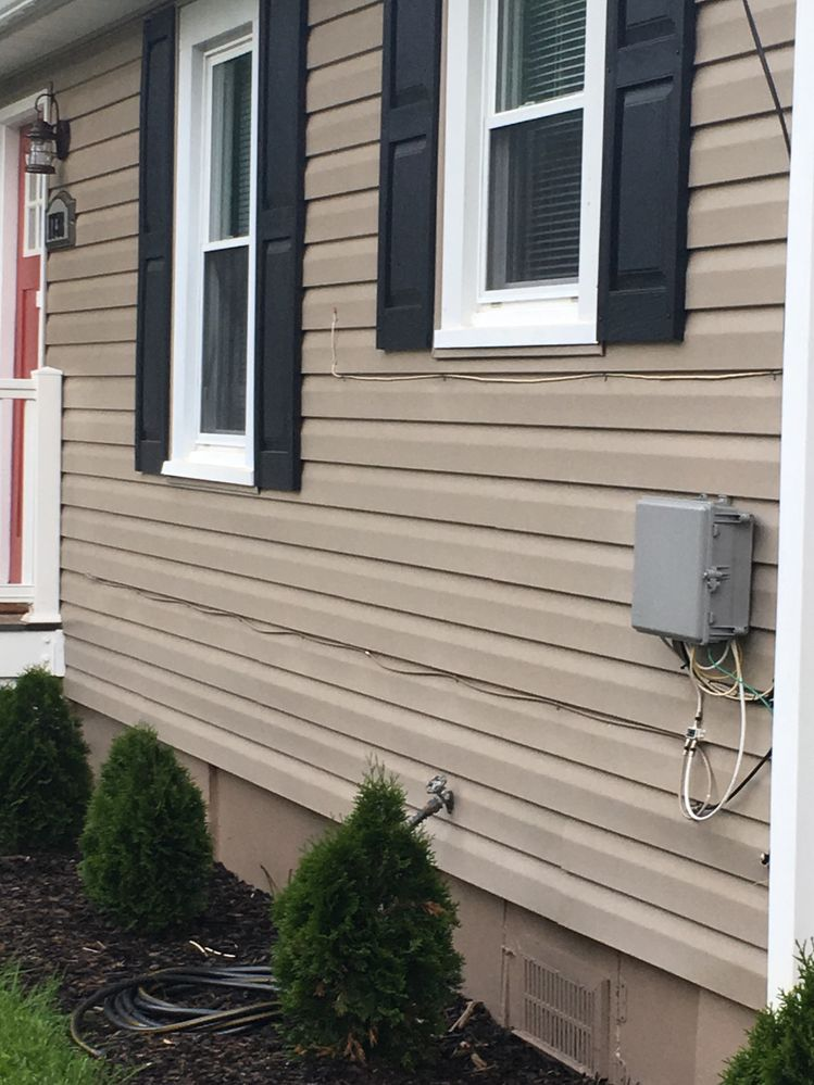 phone line between windows through the middle of the siding.